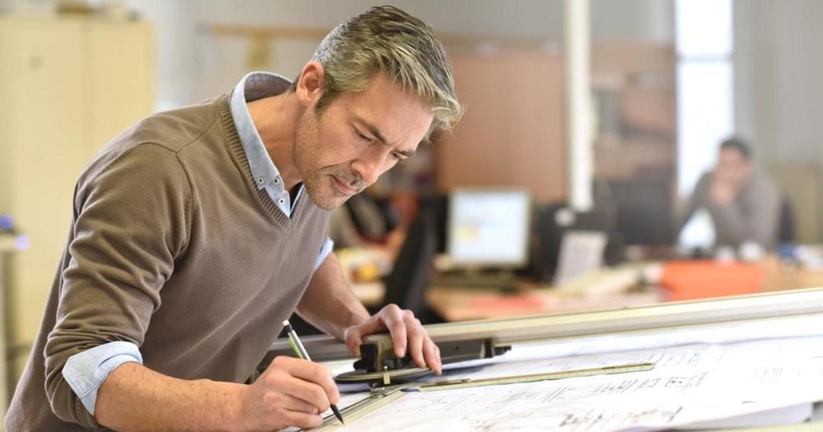 hombre-escribiendo-planos-oficina-elegir-arquitecto-especialista-generalista