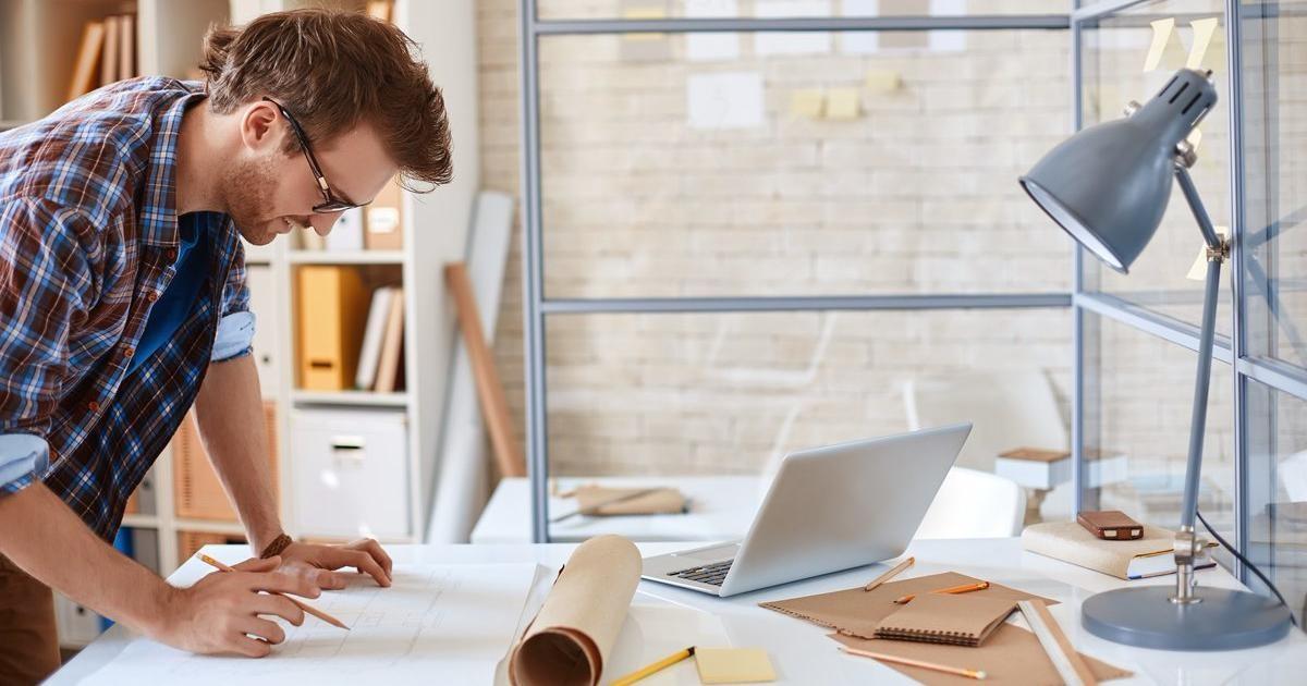 hombre-trabajando-planos-oficina-mesa-elegir-arquitecto-especialista-generalista
