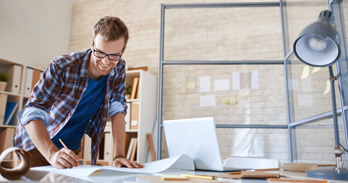 hombre-escribiendo-planos-escritorio-sala-oficina-considerar-antes-contratar-arquitecto
