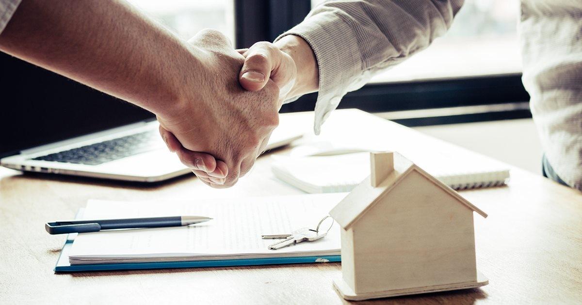 cuanto-cobra-un-arquitecto-tarifas-manos-estrechando-escritorio-casa-maqueta-lapiz-laptop